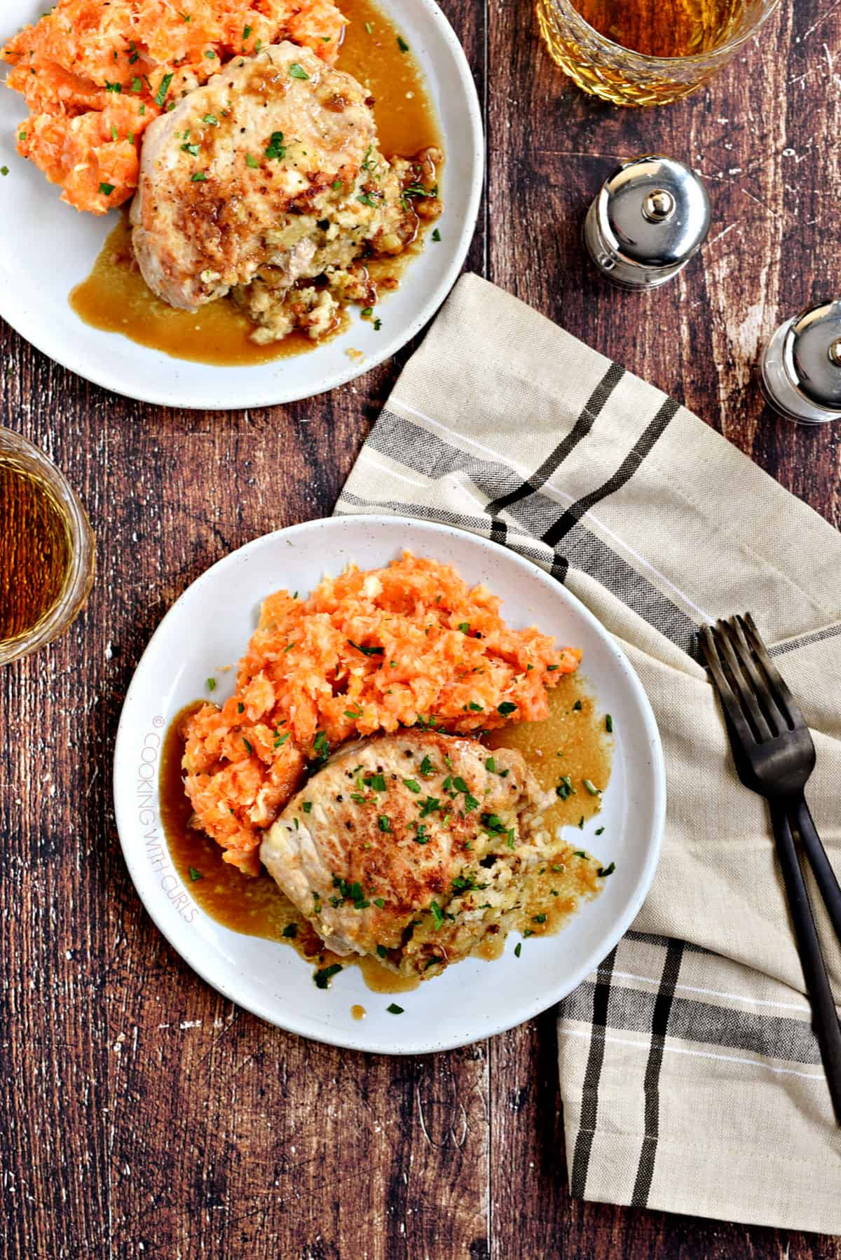 Looking down on two plates of A stuffed pork chop covered in an apple-bourbon sauce and served with carrot parsnip mash with a glass of whisky in the background.
