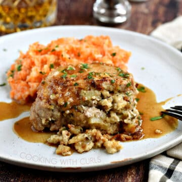 A stuffed pork chop covered in an apple-bourbon sauce and served with carrot parsnip mash on a large white plate with a glass of whisky in the background.