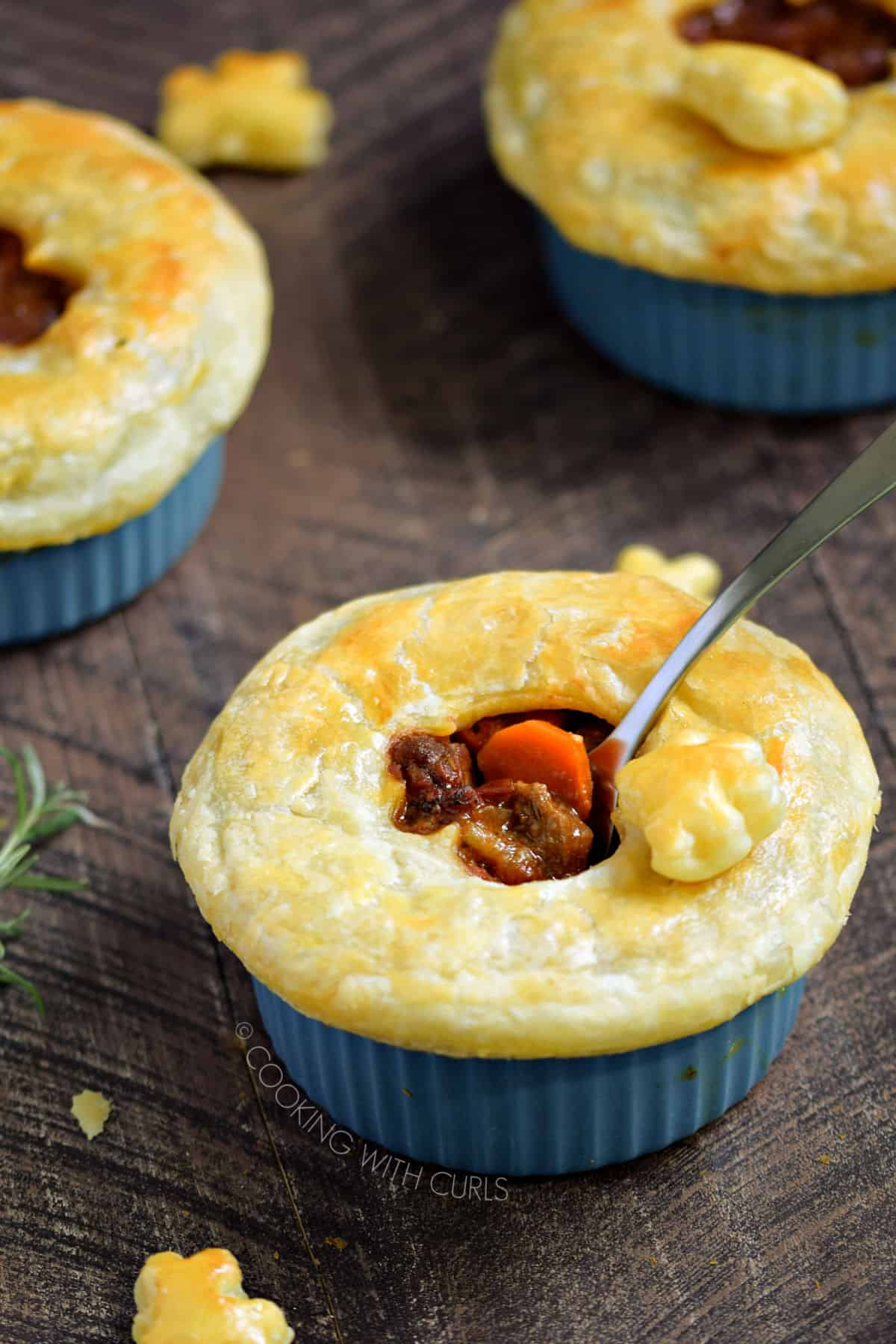 Puff pastry topped beef stew in a blue ramekin with two more in the background.