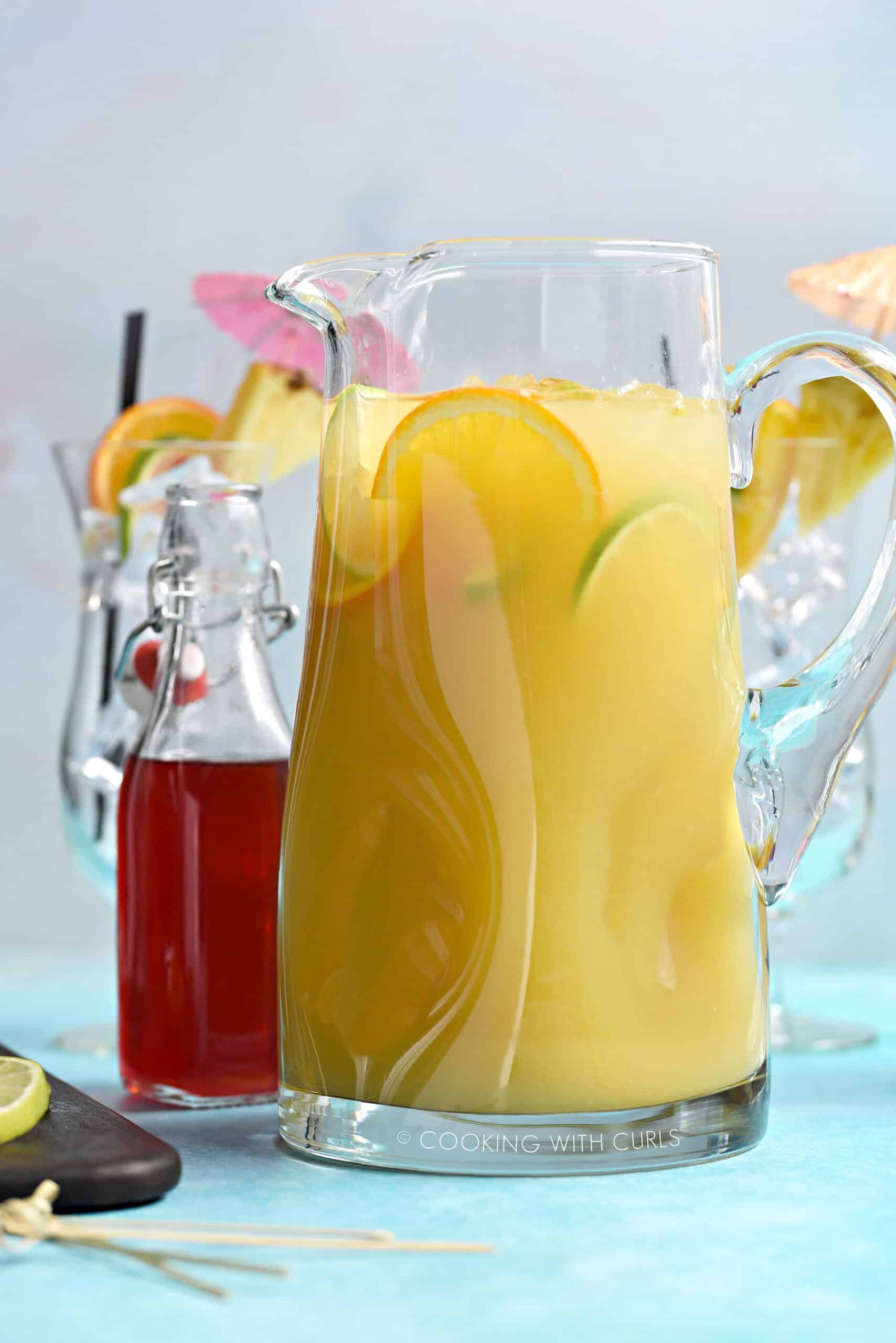 A pitcher of fruit juices and rum with two glasses filled with ice and a bottle of strawberry syrup in the background.