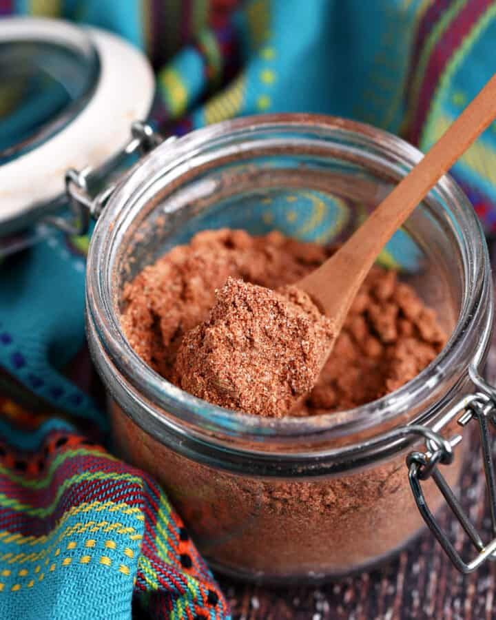 Mexican Seasoning Recipe in a small glass jar with a wooden spoon.
