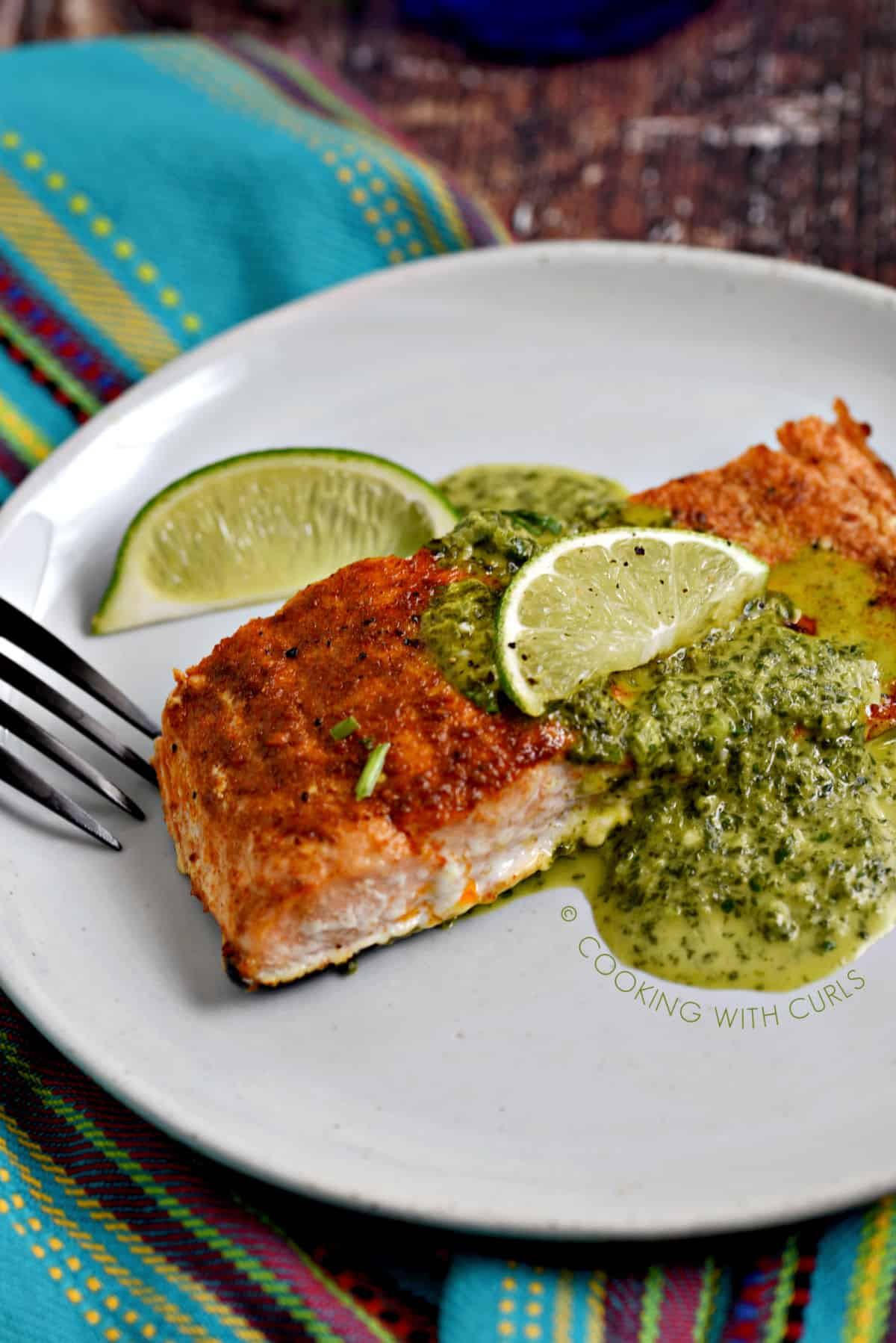 Baked Salmon topped with Cilantro Lime Sauce on a white plate with a lime wedge on the side.