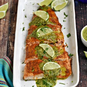 Baked salmon filet topped with cilantro sauce and lime wedges on a white platter.