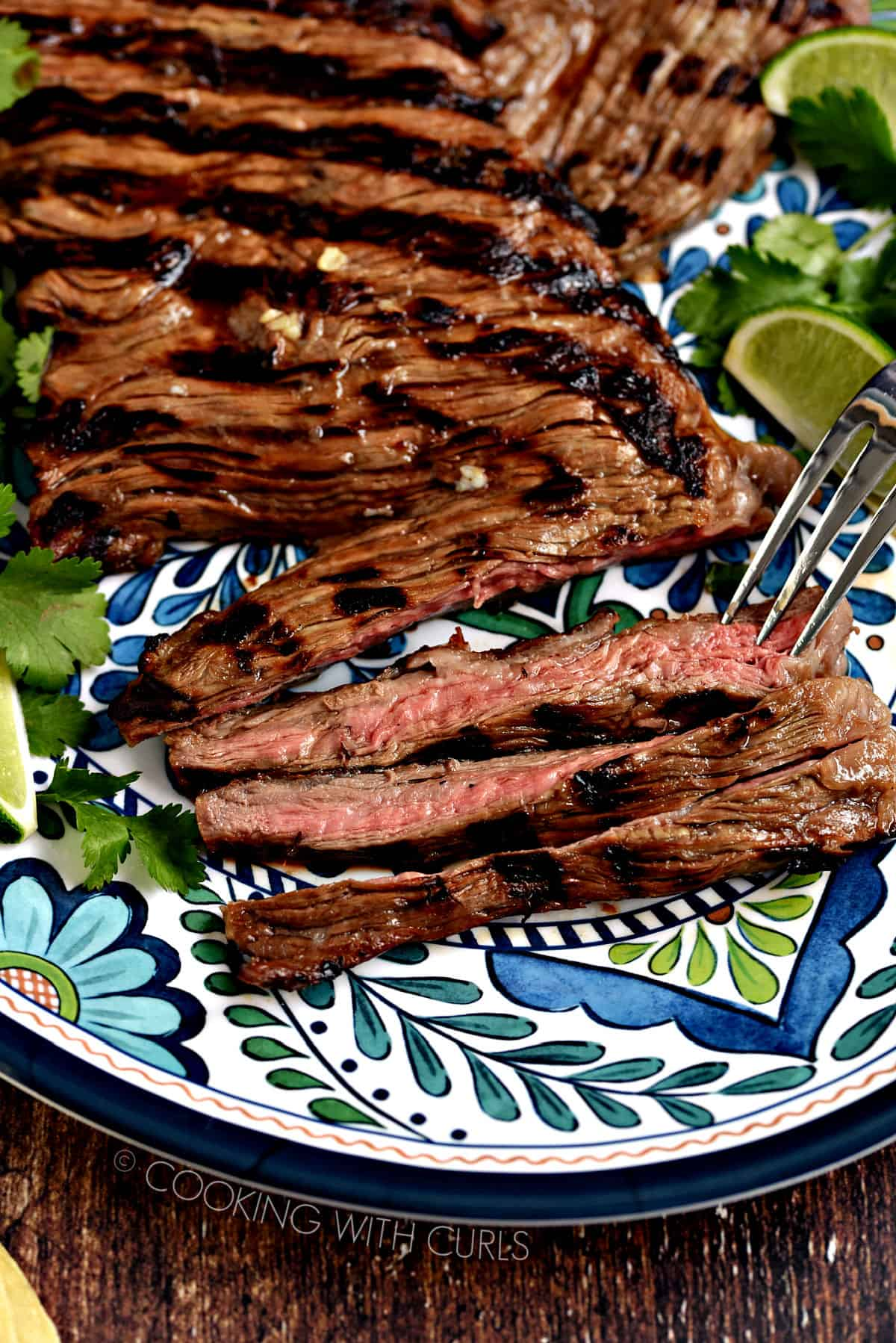 Grilled skirt steak on a decorative platter with lime wedges and cilantro leaves.