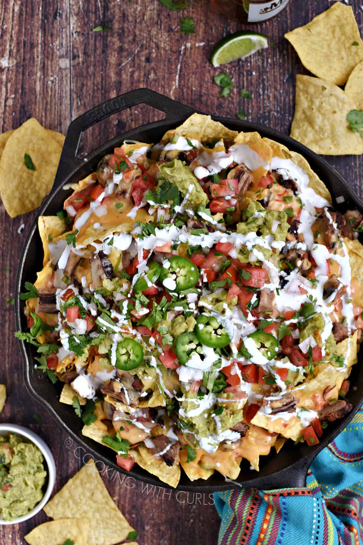 Looking down on Carne Asada Nachos in a cast iron skillet topped with crema, jalapeno and guacamole with chips scattered around and a bowl of guacamole in the background.