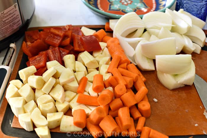 Chopped red bell pepper, parsnip, carrots, and wedged onions on a cutting board.