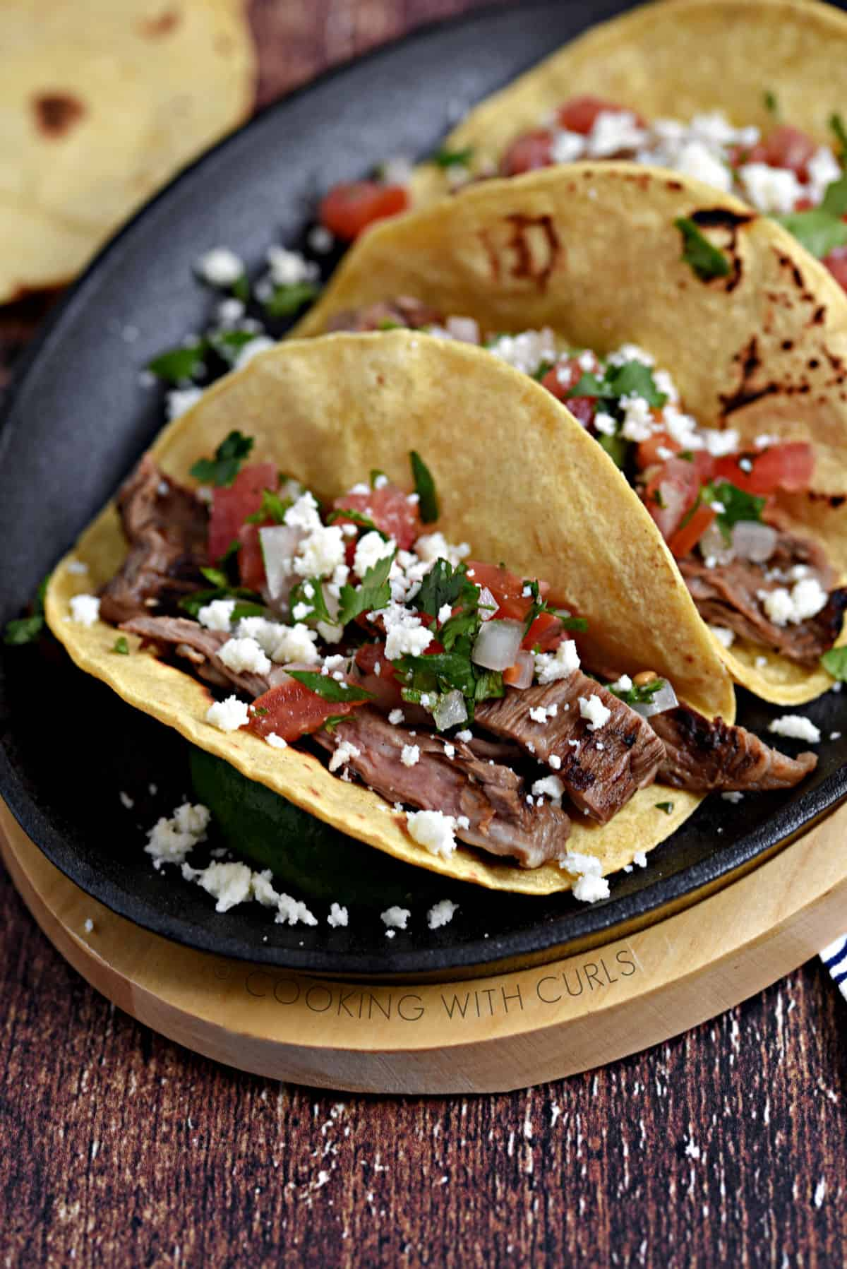 Corn tortillas filled with steak, diced tomatoes and onions sprinkled with queso crumbles and cilantro on a skillet.