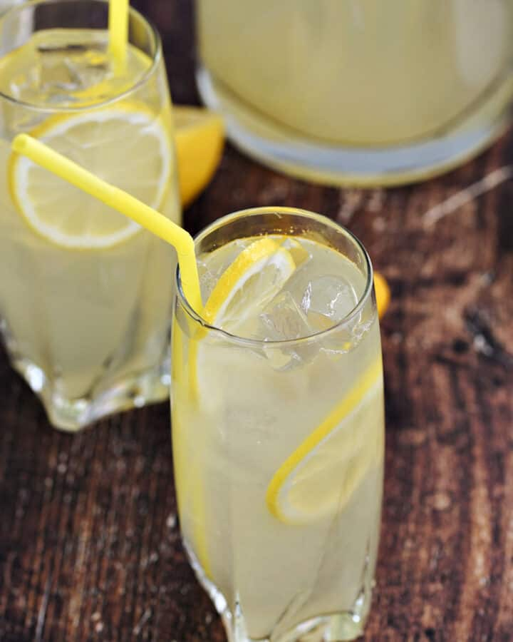 Two glasses and one glass pitcher filled with lemonade and lemon slices and yellow straws.