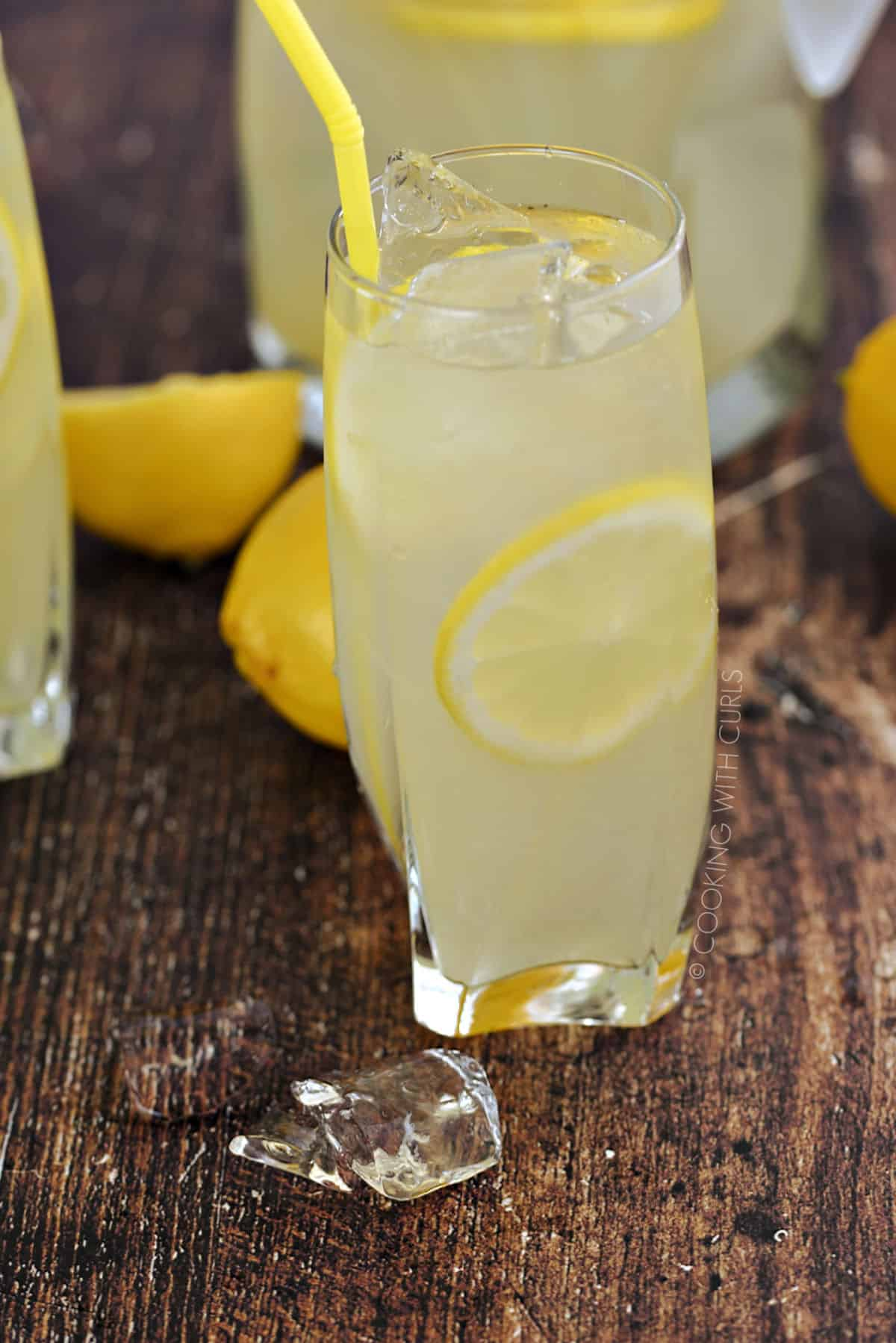 A big glass of lemonade, ice cubes and lemon slices with a pitcher and fresh lemons in the background.