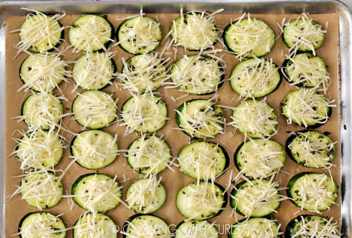Grated Parmesan cheese topped zucchini slices on a parchment lined baking sheet.