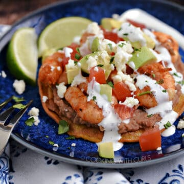 Shrimp, diced tomatoes, onions and avocado on a bed of refried beans on a corn tortilla drizzled with crema and crumbled cheese on a blue plate.