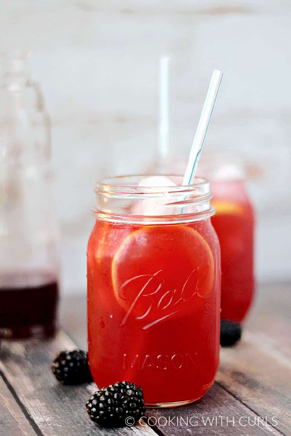 Two mason jars filled with blackberry lemonade with fresh berries on the surface and bottle of syrup in the background.