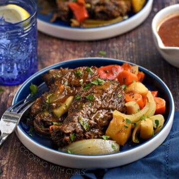 Pot roast with carrots, onions and parsnips on a blue plate with a blue glass and blue napkin in the background.