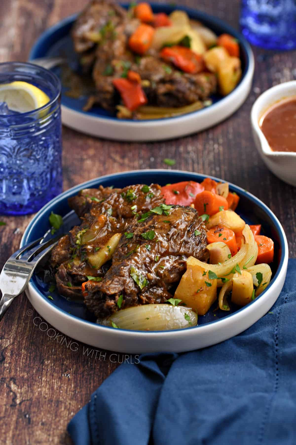 Pot roast topped with gravy and served with chopped red bell peppers, carrots, parsnips and onion wedges on a blue plate.