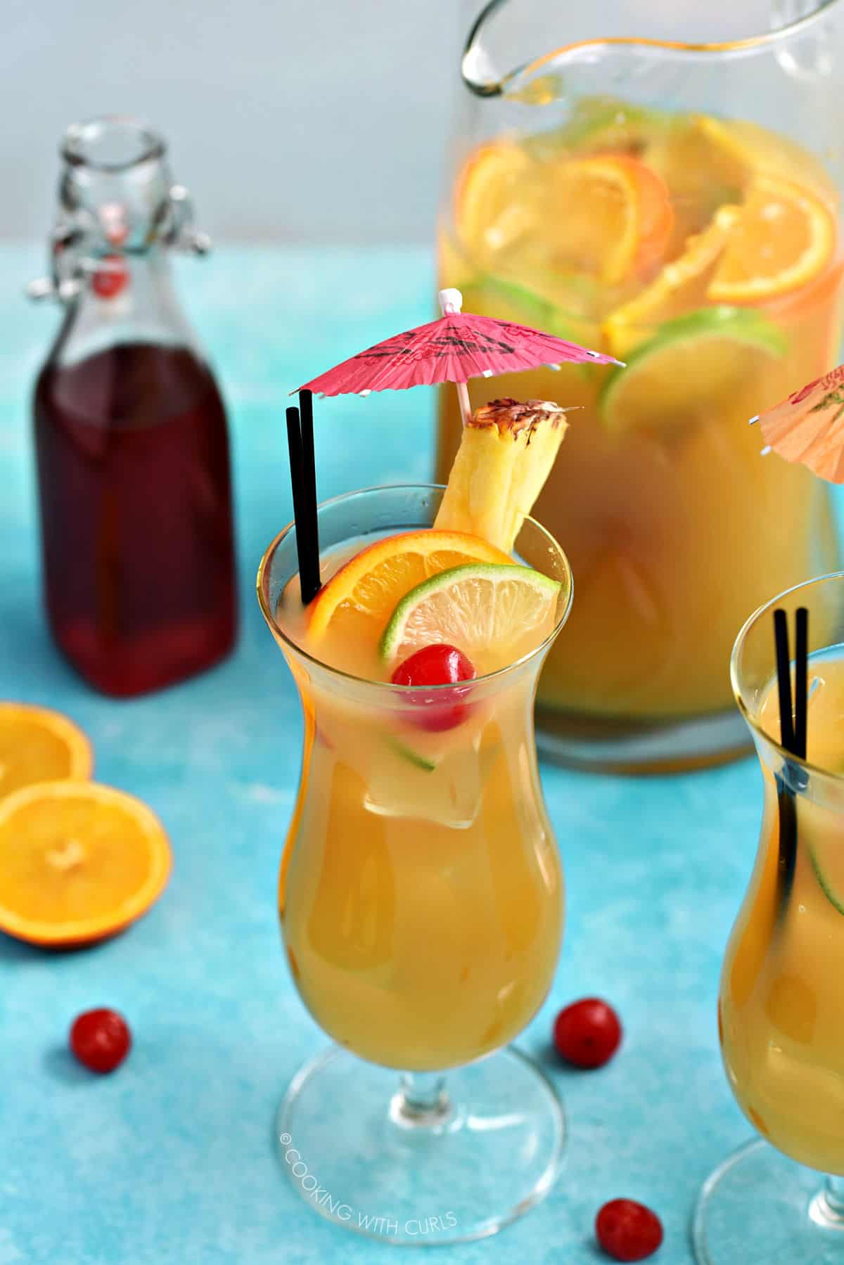 Two hurricane glasses filled with Jamaican Rum Punch with a pitcher of punch and bottle of strawberry syrup in the background.