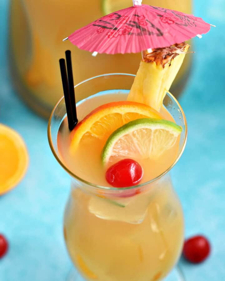 A hurricane glass filled with Jamaican Rum Punch and garnished with slices of orange and lime with a cherry and a pineapple slice with a pink paper umbrella on the rim.