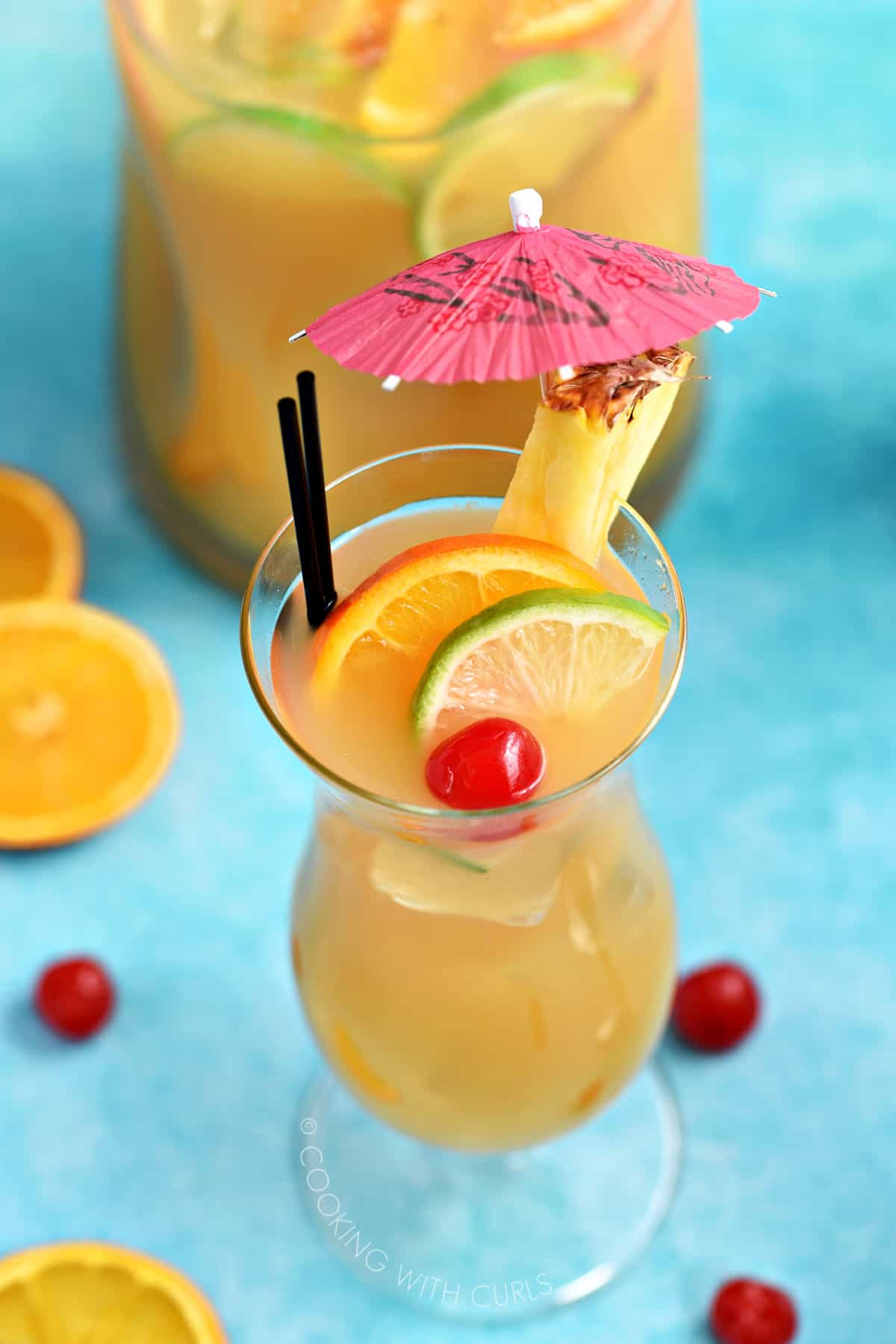 Hurricane glass filled with fruit punch, garnished with slices of orange and lime with a cherry and a pineapple slice with a pink paper umbrella on the rim.