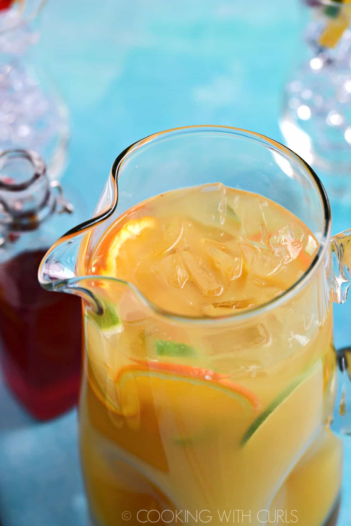 Looking down into a pitcher of Jamaican Rum Punch with ice cubes and fresh fruit and a bottle of strawberry syrup in the background.