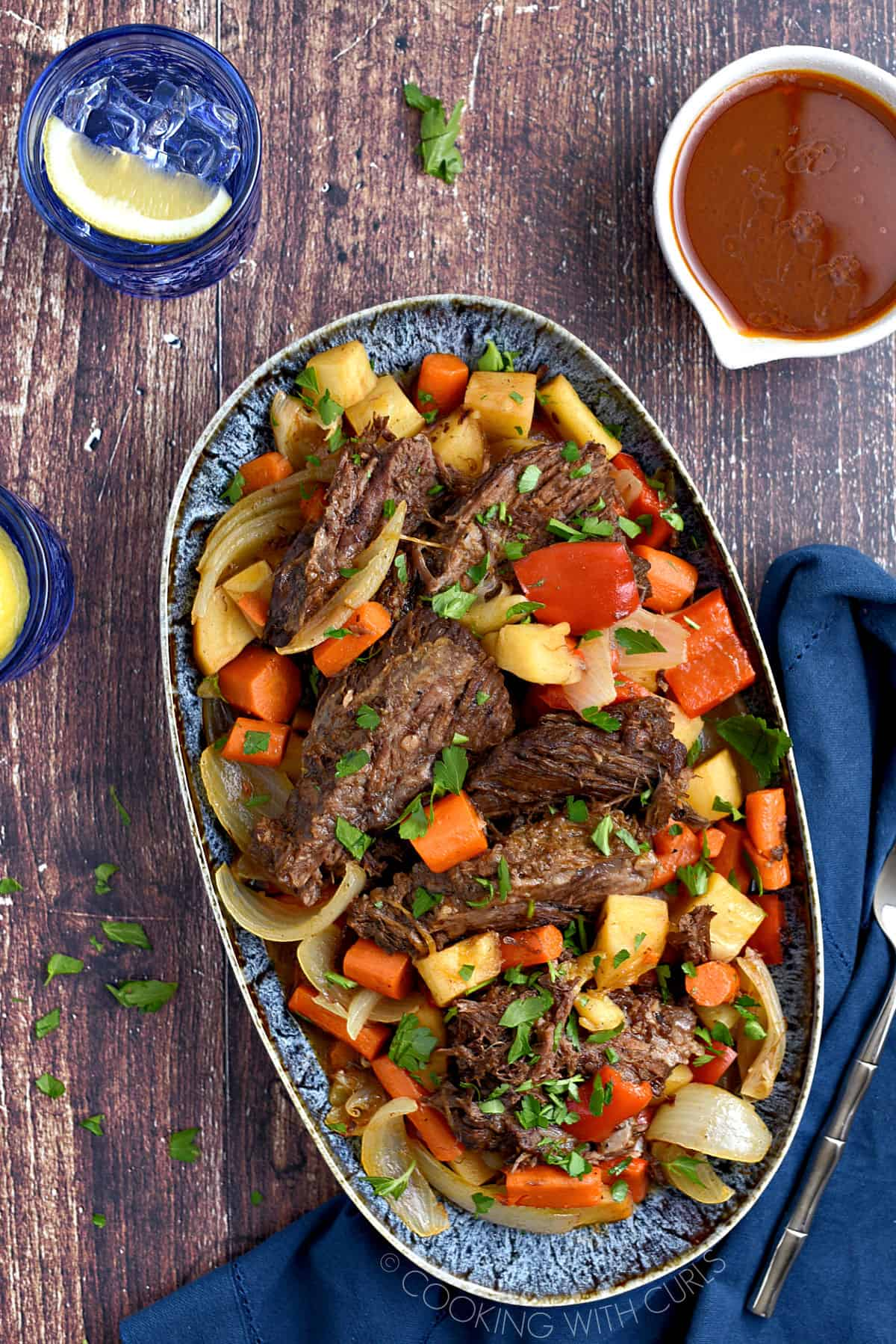 Looking down on a platter filled with Instant Pot Moroccan Pot Roast and vegetables with a blue glass of water and a white bowl of gravy in the background.