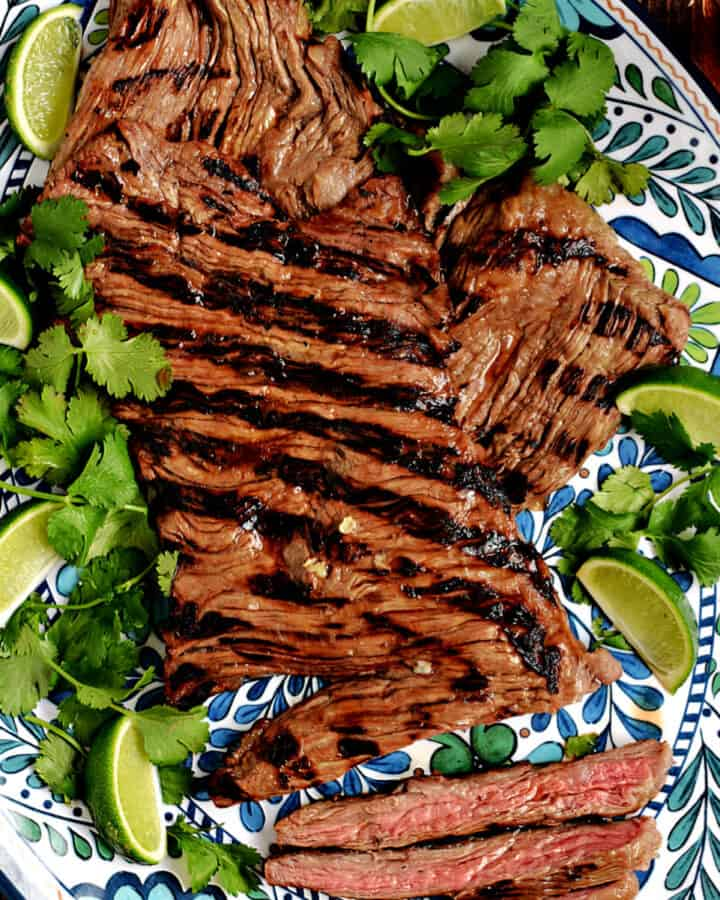 Grilled skirt steak on a platter with lime wedges and cilantro leaves.