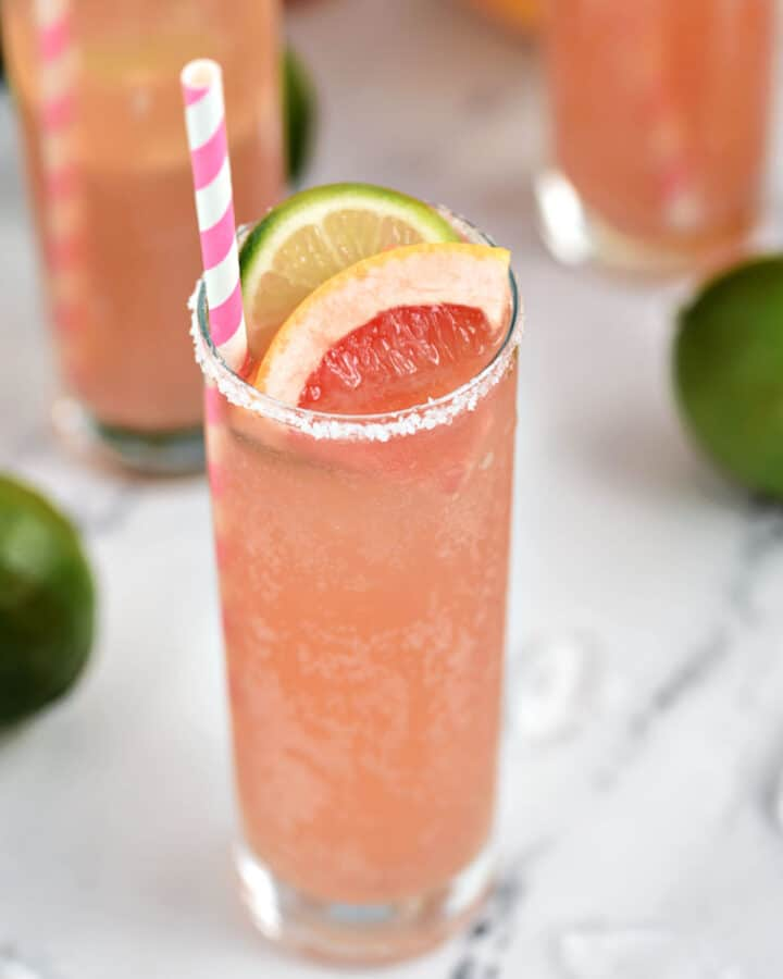 A bubbly, pink cocktail in a tall glass garnished with a slice of lime and grapefruit and a pink and white striped straw.