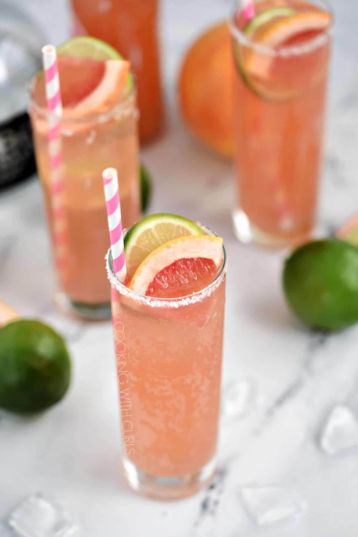 Three bubbly, pink cocktails in tall glasses garnished with a slice of lime and grapefruit with a pink and white striped straw.