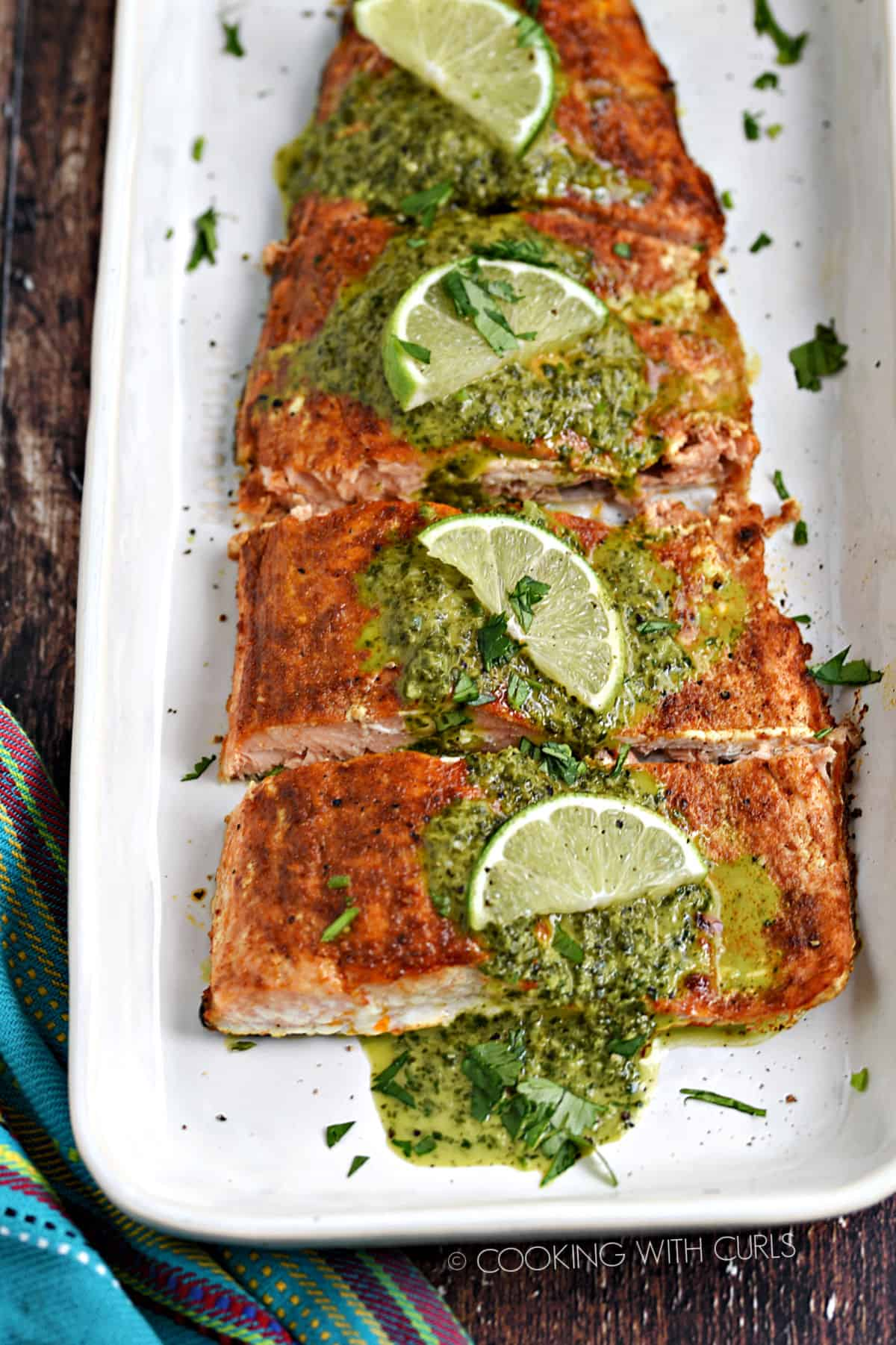 Baked salmon filet topped with cilantro lime sauce on a white platter.