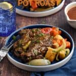 Pot roast topped with gravy and served with chopped red bell peppers, carrots, parsnips and onion wedges on a blue plate with title graphic across the top.