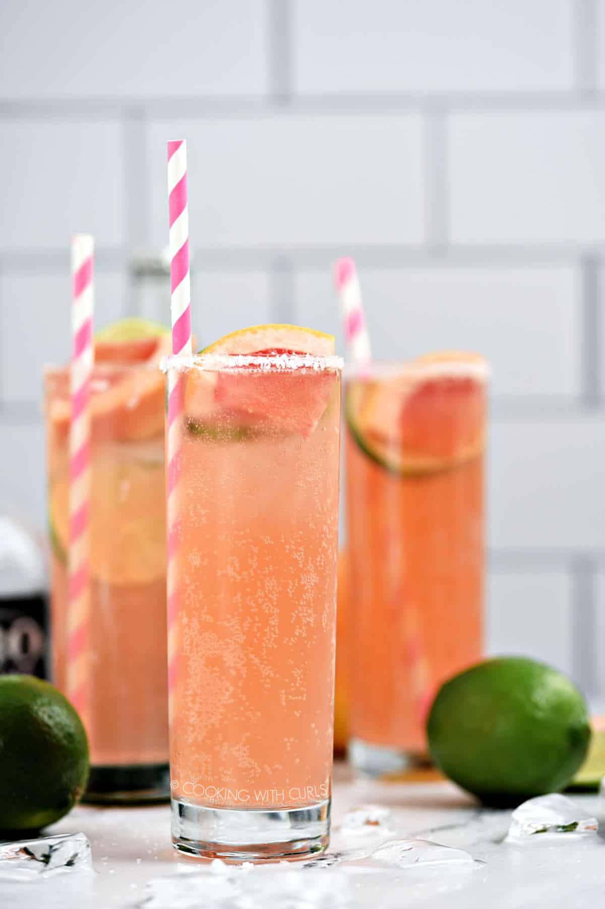 Three bubbly, pink Paloma cocktails in tall glasses garnished with a slice of lime and grapefruit with a pink and white striped straw.