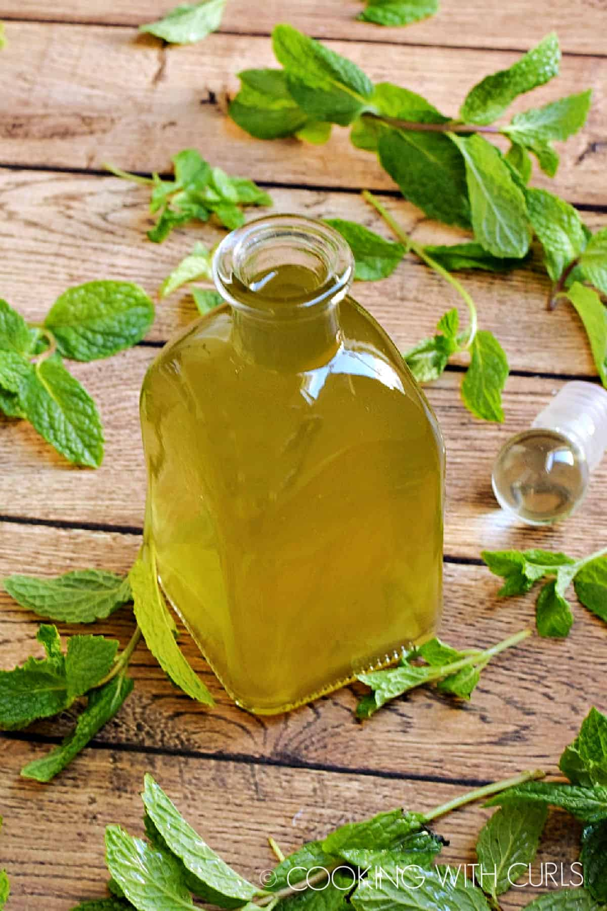 a square glass bottle of peppermint syrup surrounded by fresh mint sprigs on a wooden background.