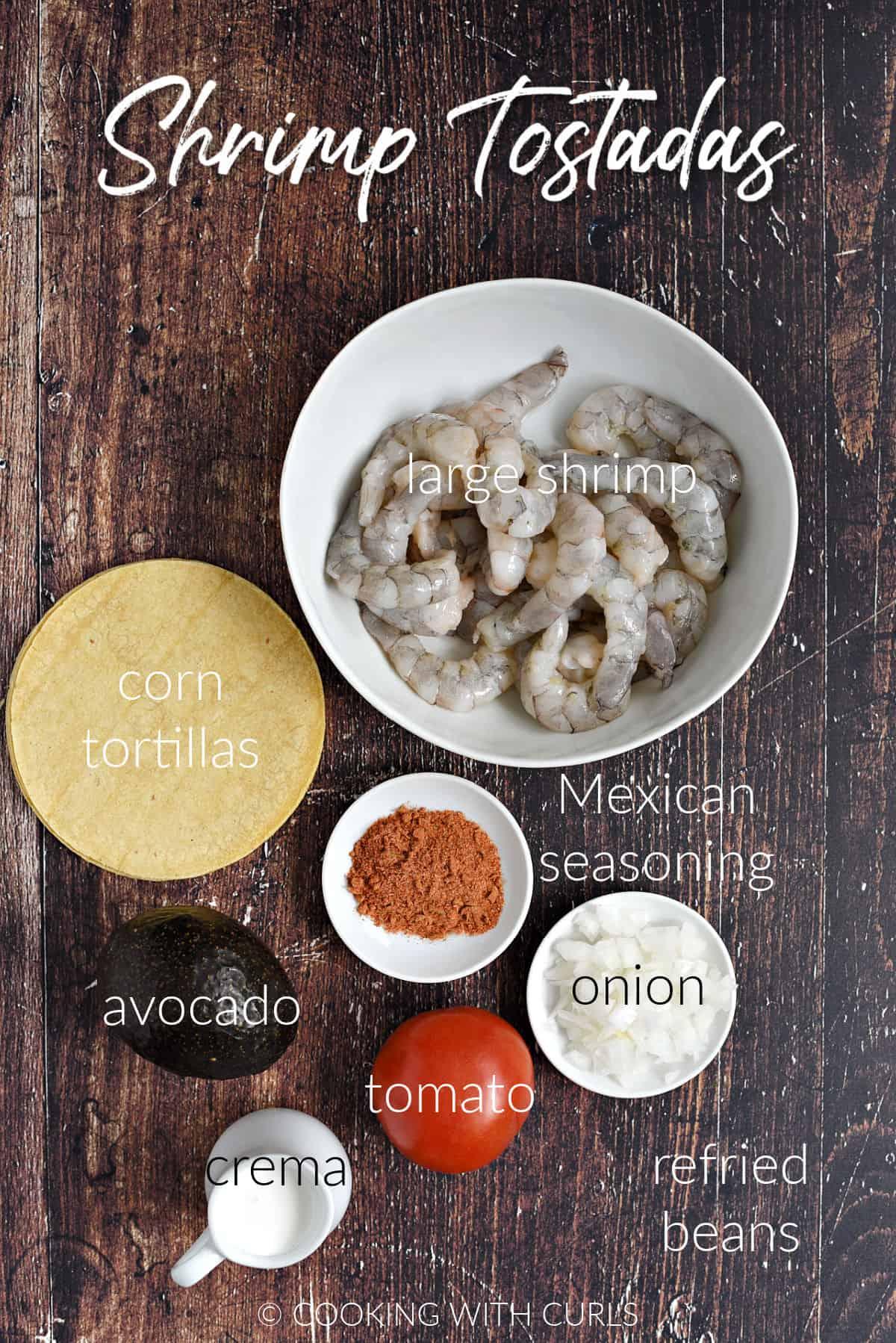Raw shrimp, corn tortillas, avocado, crema, onion, tomato and seasoning for Shrimp Tostadas.