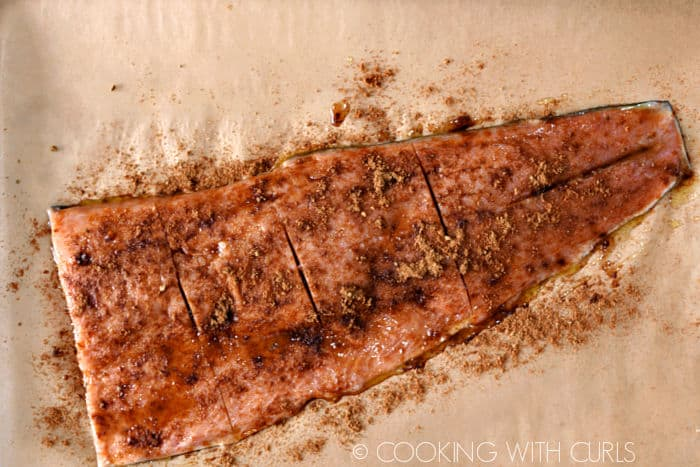 Spices sprinkled over salmon filet on a parchment lined baking sheet.