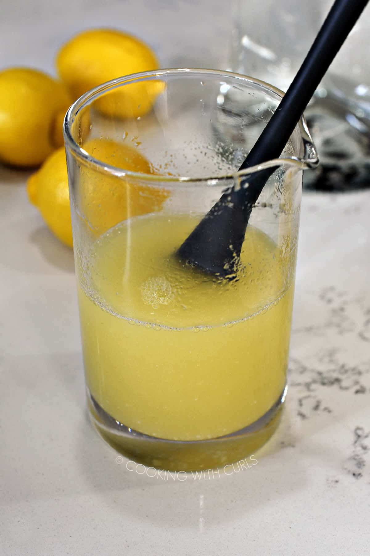 Sugar dissolved in lemon juice, stirred with a gray silicone mini spatula in a glass measuring cup.