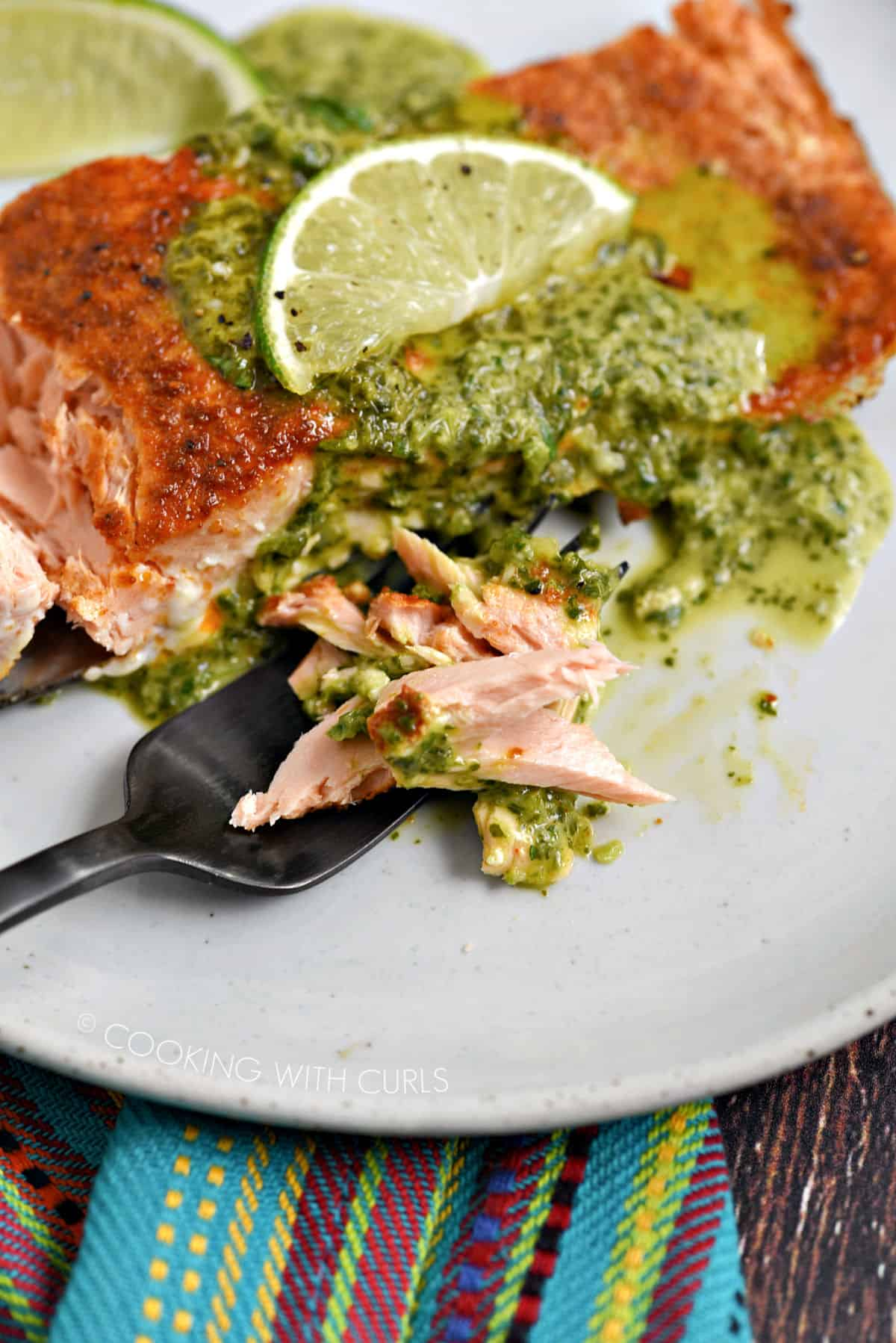 Flaky salmon on a black fork with a salmon filet topped with cilantro sauce and lime slice on a white plate.