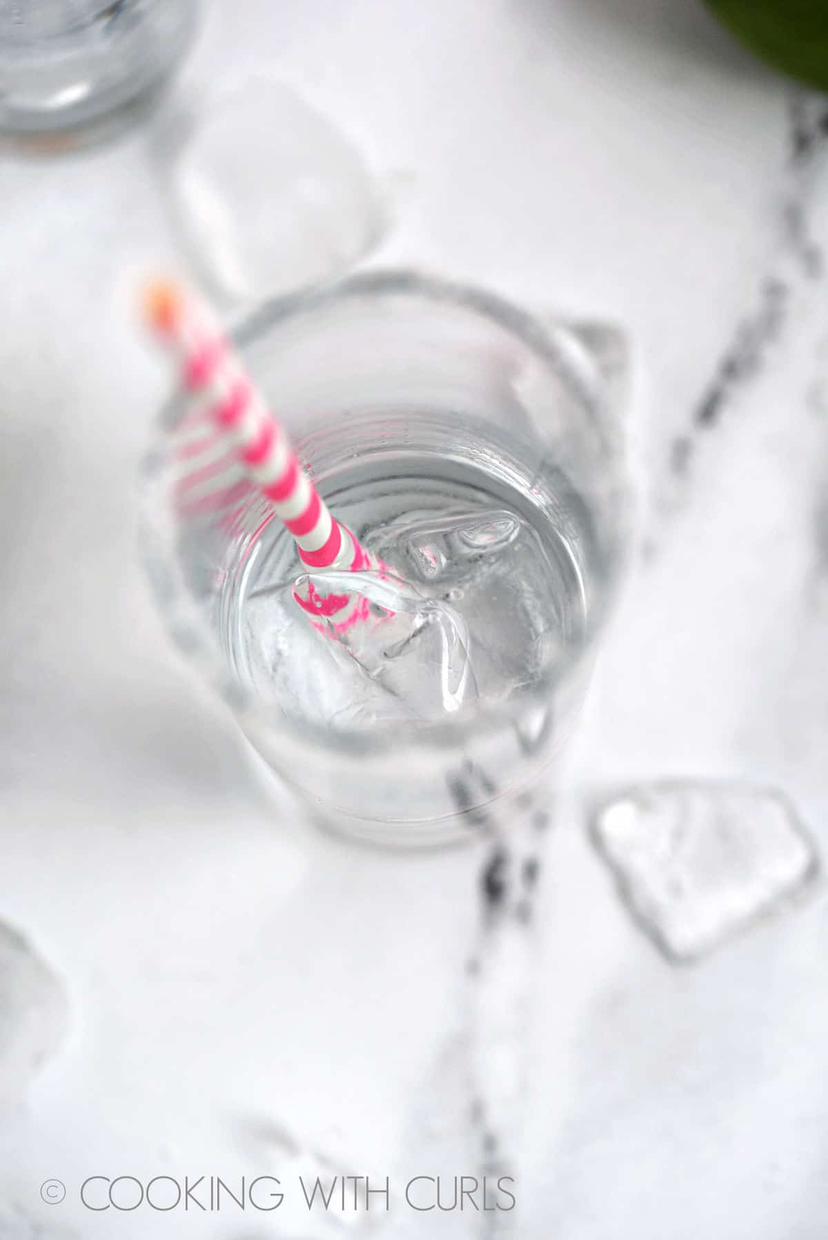 Tequila in a highball glass with ice cubes and pink and white striped straw.