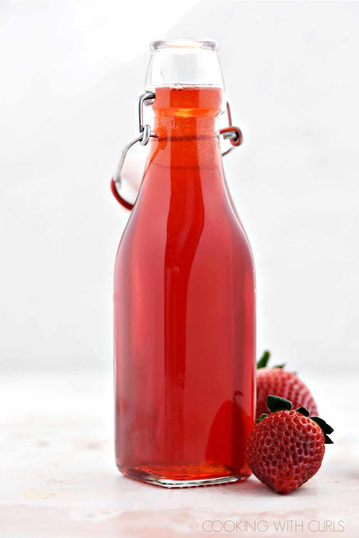 Close-up image of Strawberry Simple Syrup in a square bottle with two fresh strawberries around the base of the bottle.