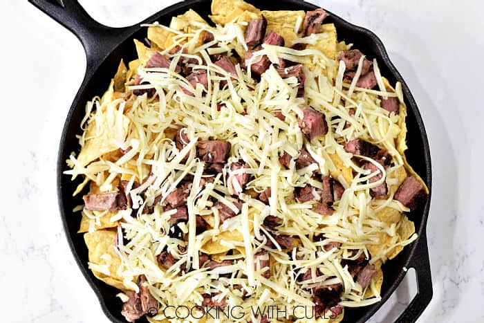 Tortilla chips, grated cheese and chunks of steak in a cast iron skillet.