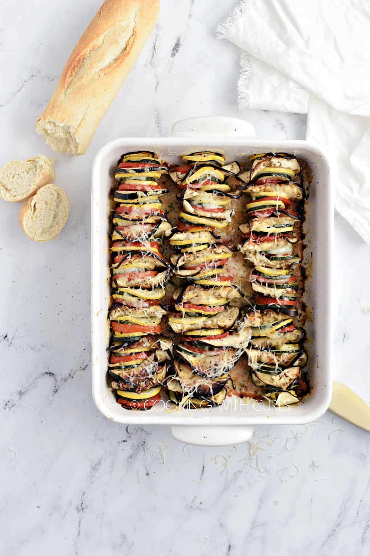 Vegetable Tian Recipe in a white baking dish with a loaf of bread in the background.