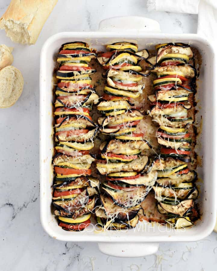 Slices of zucchini, yellow squash, eggplant and tomatoes lined up in a white baking dish topped with melted cheese.