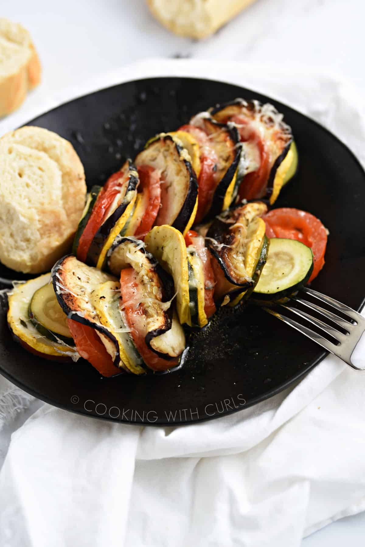 Vegetable Tian on a black plate with a slice of bread.