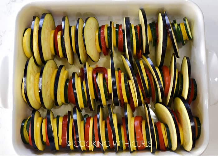 Zucchini, squash, tomatoes and eggplant slices lined up in a white baking dish.