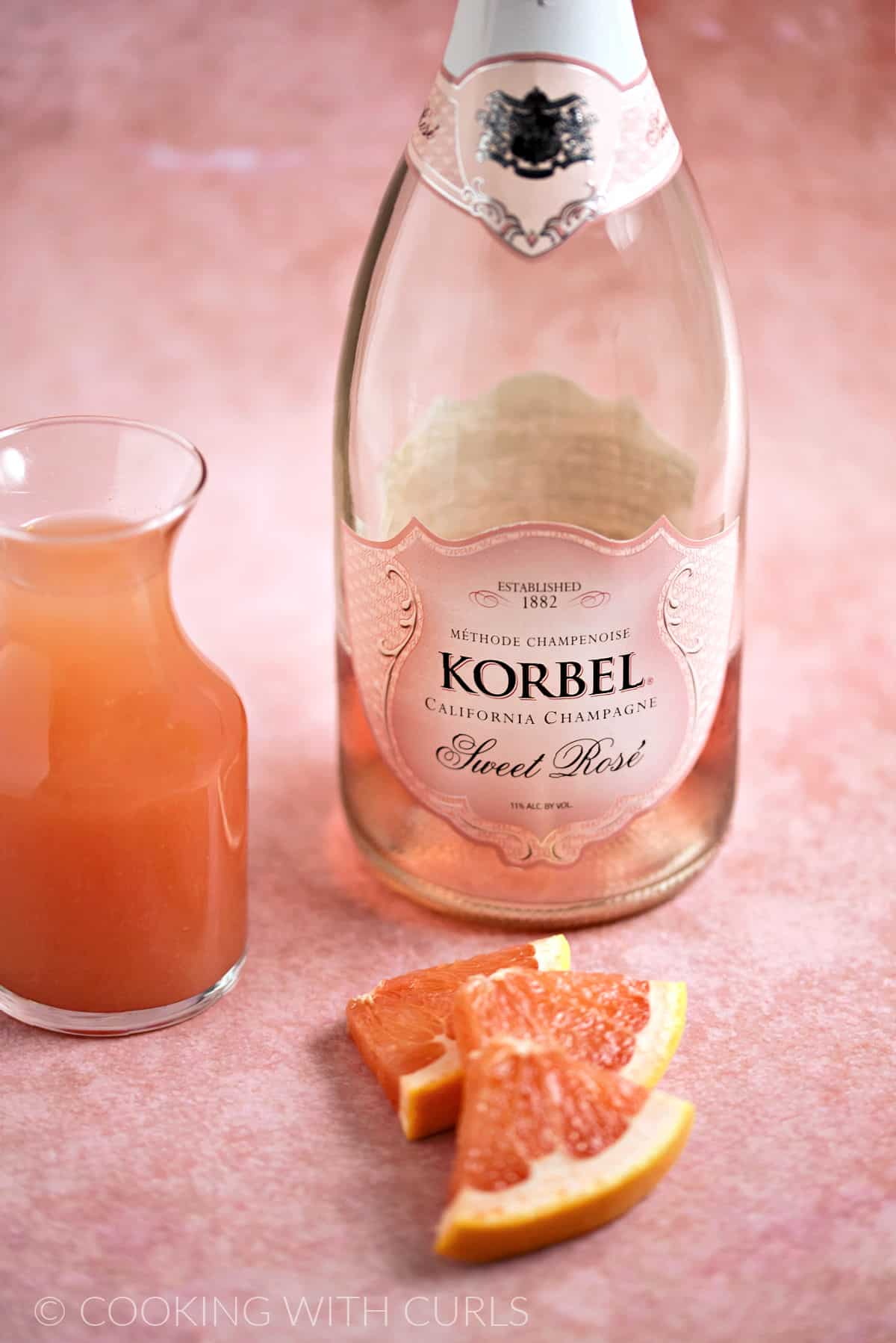 A bottle of rose champagne, a small carafe of red grapefruit juice and three red grapefruit wedges with a pink background.