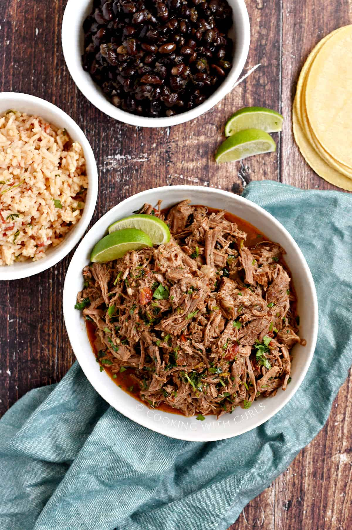 A bowl of shredded beef, rice, and black beans with corn tortillas on the side.