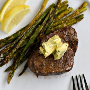 Air Fryer Steak and Asparagus topped with garlic butter on a white plate.