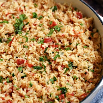 Mexican rice in a white cast iron skillet .