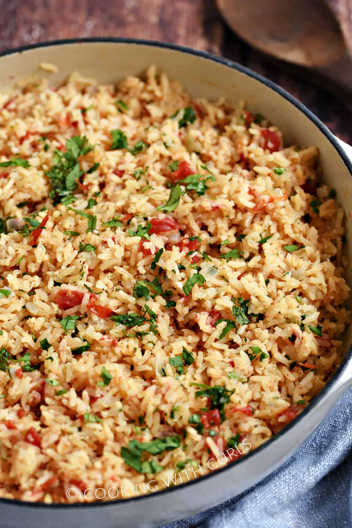 Rice, tomatoes, onions and cilantro in a large, white skillet.