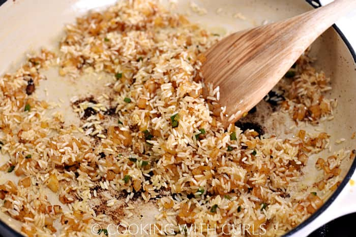 Browning rice with the sautéed onions in a skillet.