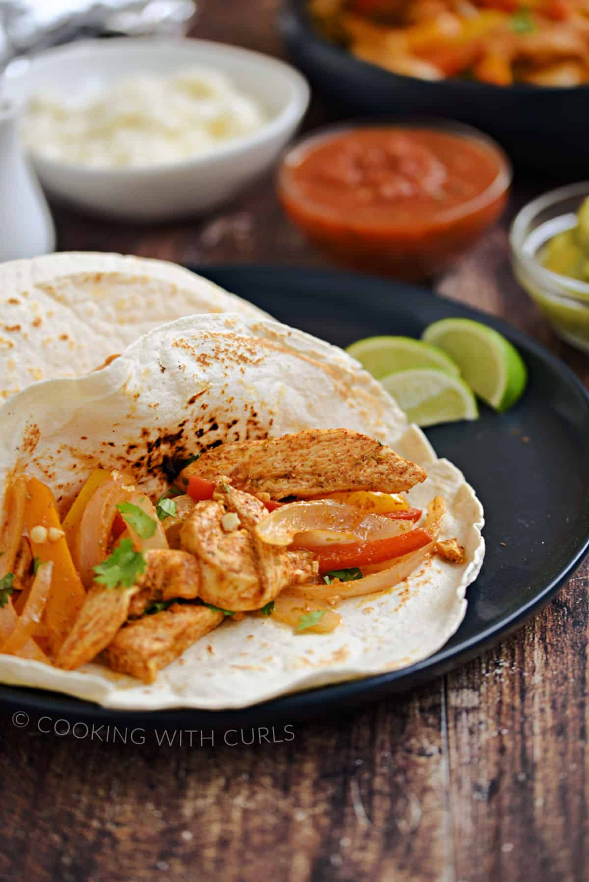 Chicken, onion, and bell pepper strips in flour tortillas with bowls of queso, salsa, and avocado in the background.