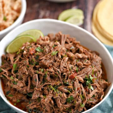 A bowl of Mexican shredded beef surrounded by bowls of rice and black beans, with corn tortillas in the background.