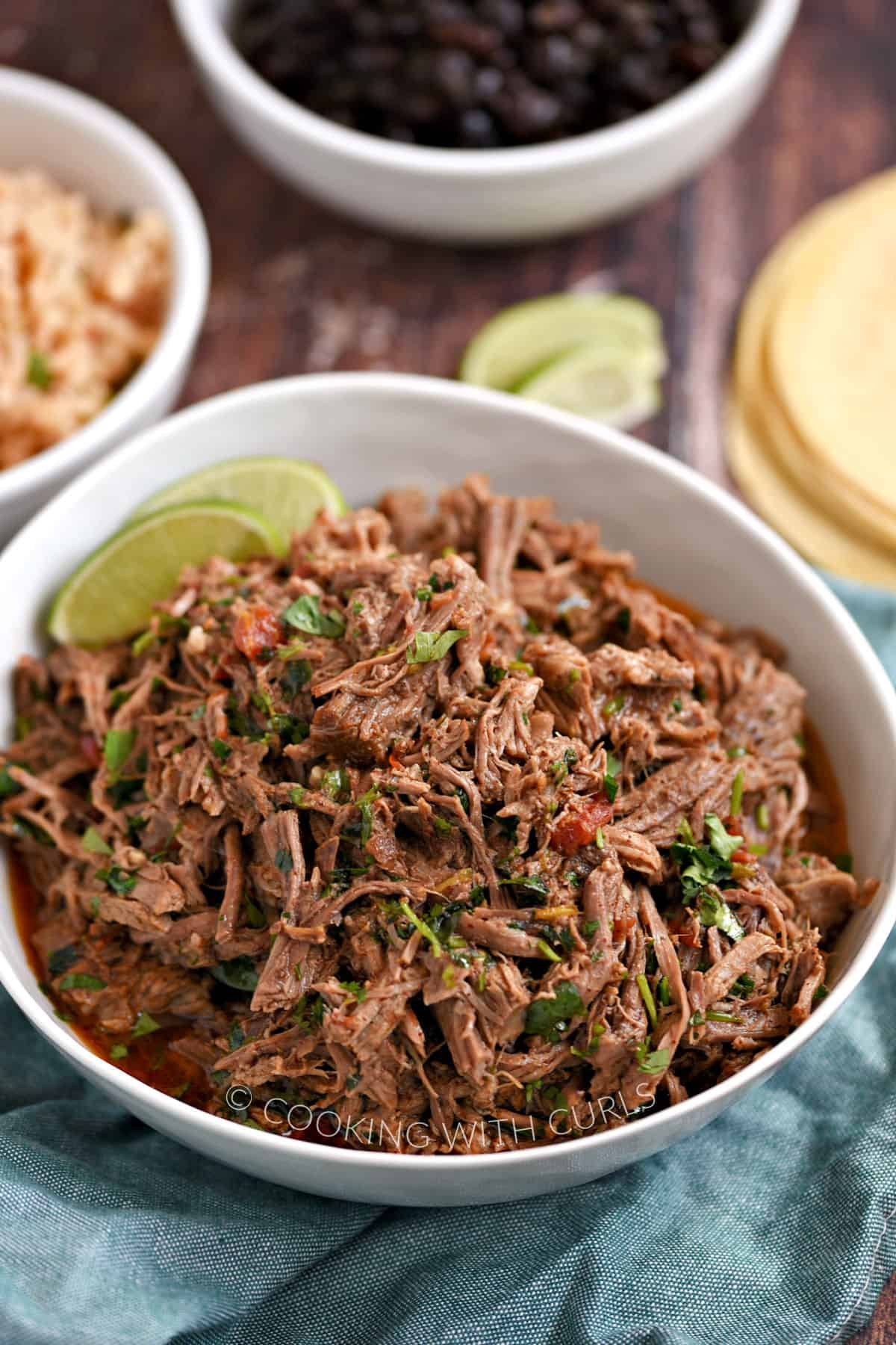 Shredded beef in a white bowl with corn tortillas and bowls of rice and black beans in the background.